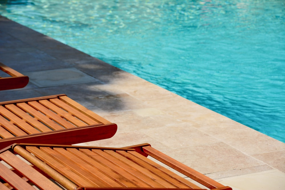 brown wooden chair near swimming pool during daytime