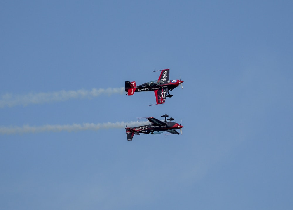 red and black jet plane in mid air during daytime