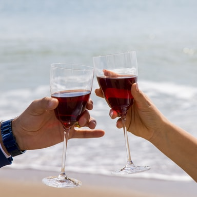 2 person holding clear wine glass with red wine during daytime