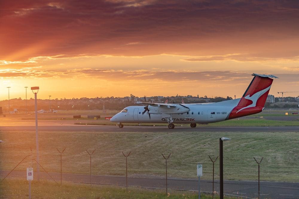 white passenger plane on airport during sunset