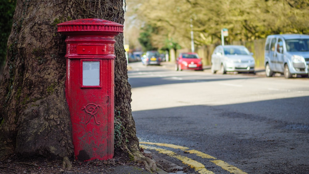 red mail box on road during daytime