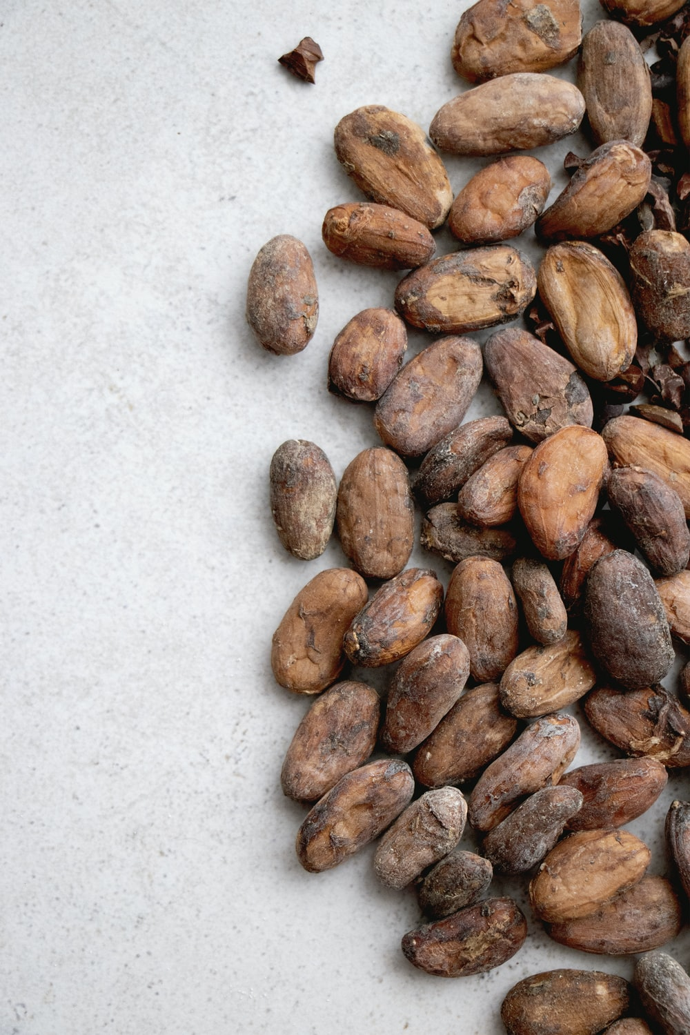 brown almond nuts on white surface