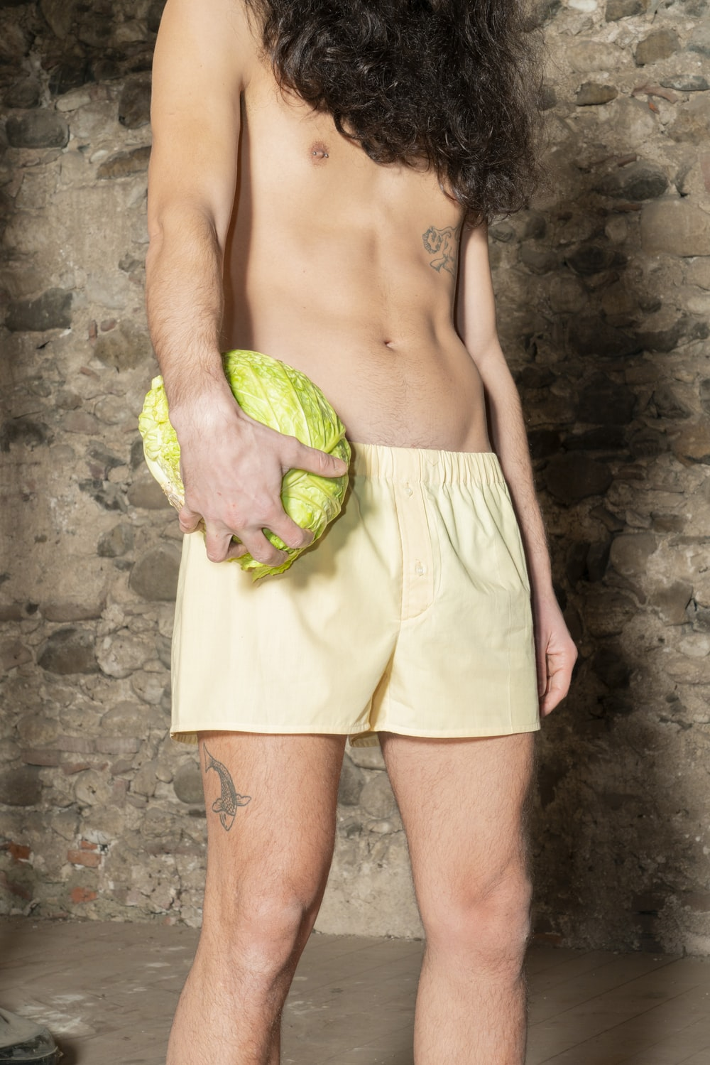 topless man in white shorts holding green textile