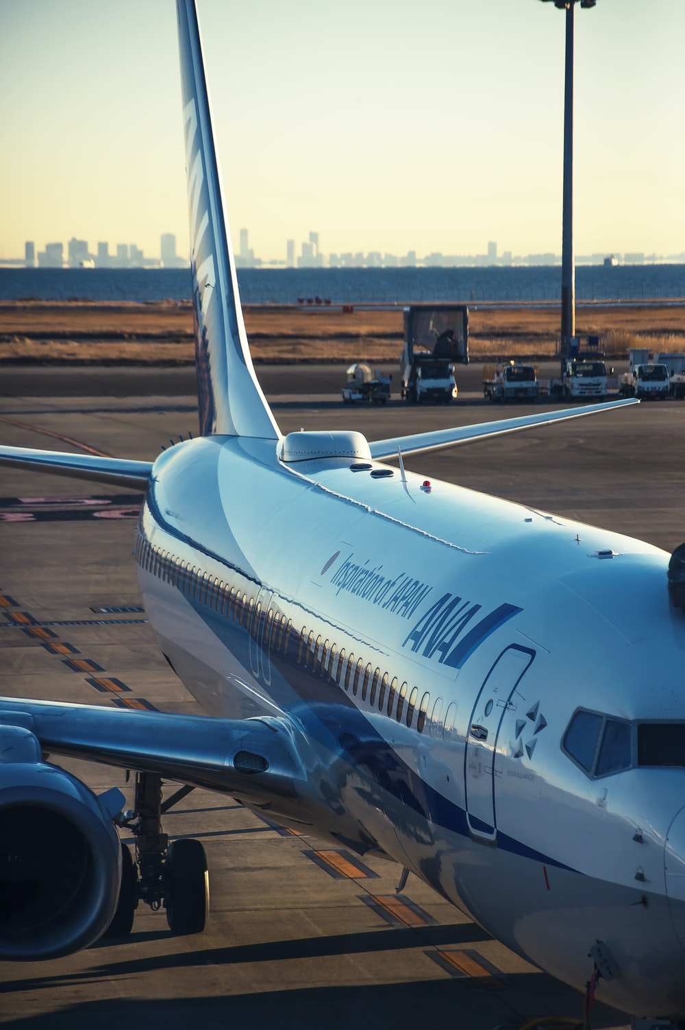 white and blue airplane on airport during daytime