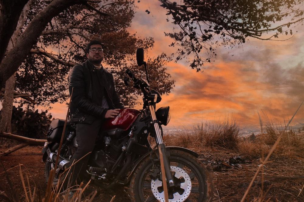 man in black jacket riding motorcycle during sunset