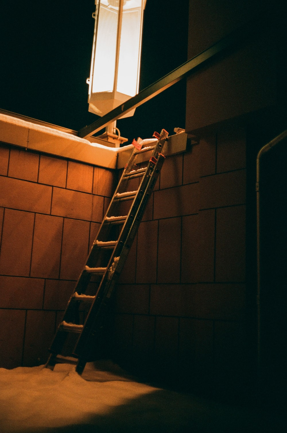 brown brick wall with black metal staircase