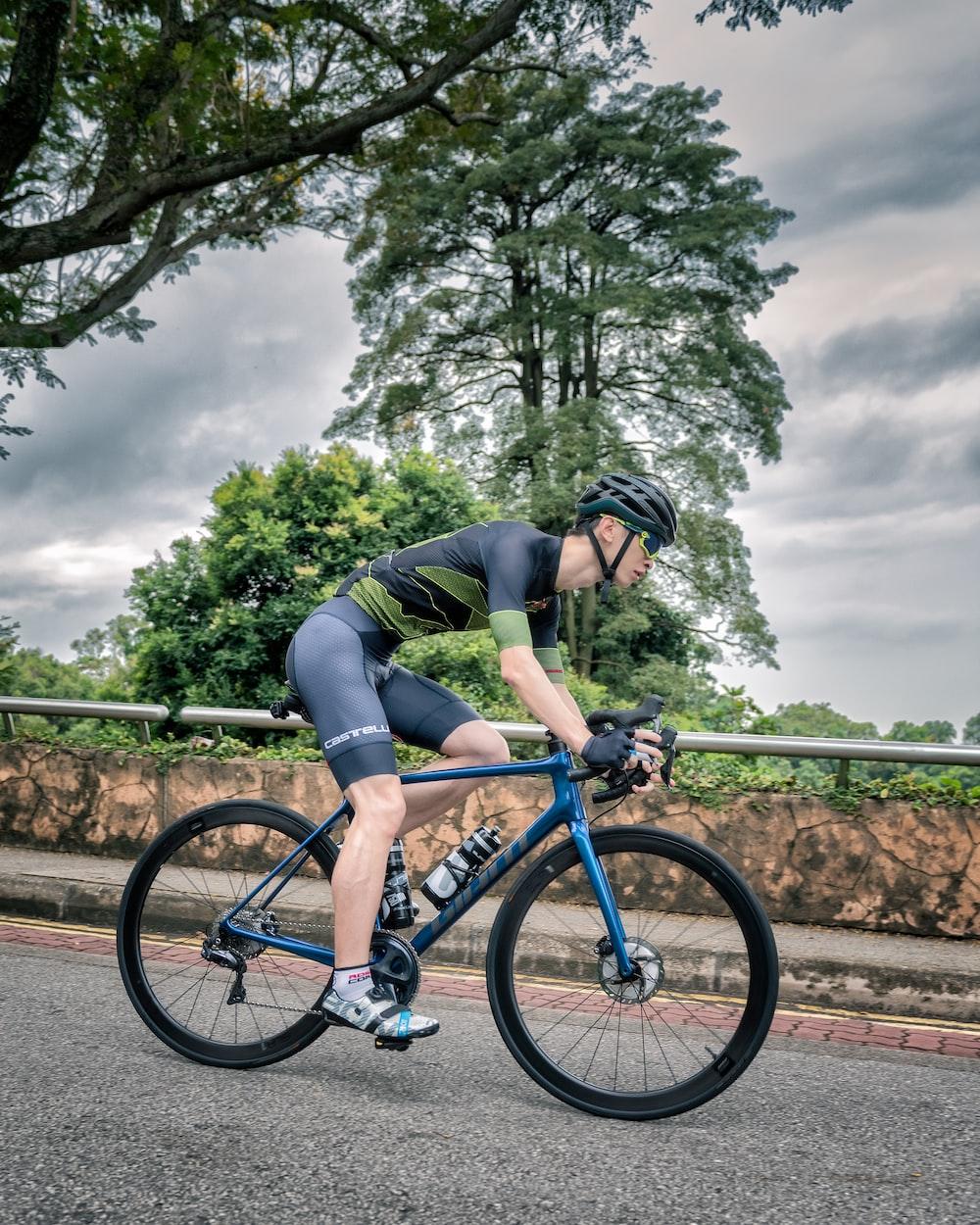 man in black shirt and black shorts riding blue mountain bike
