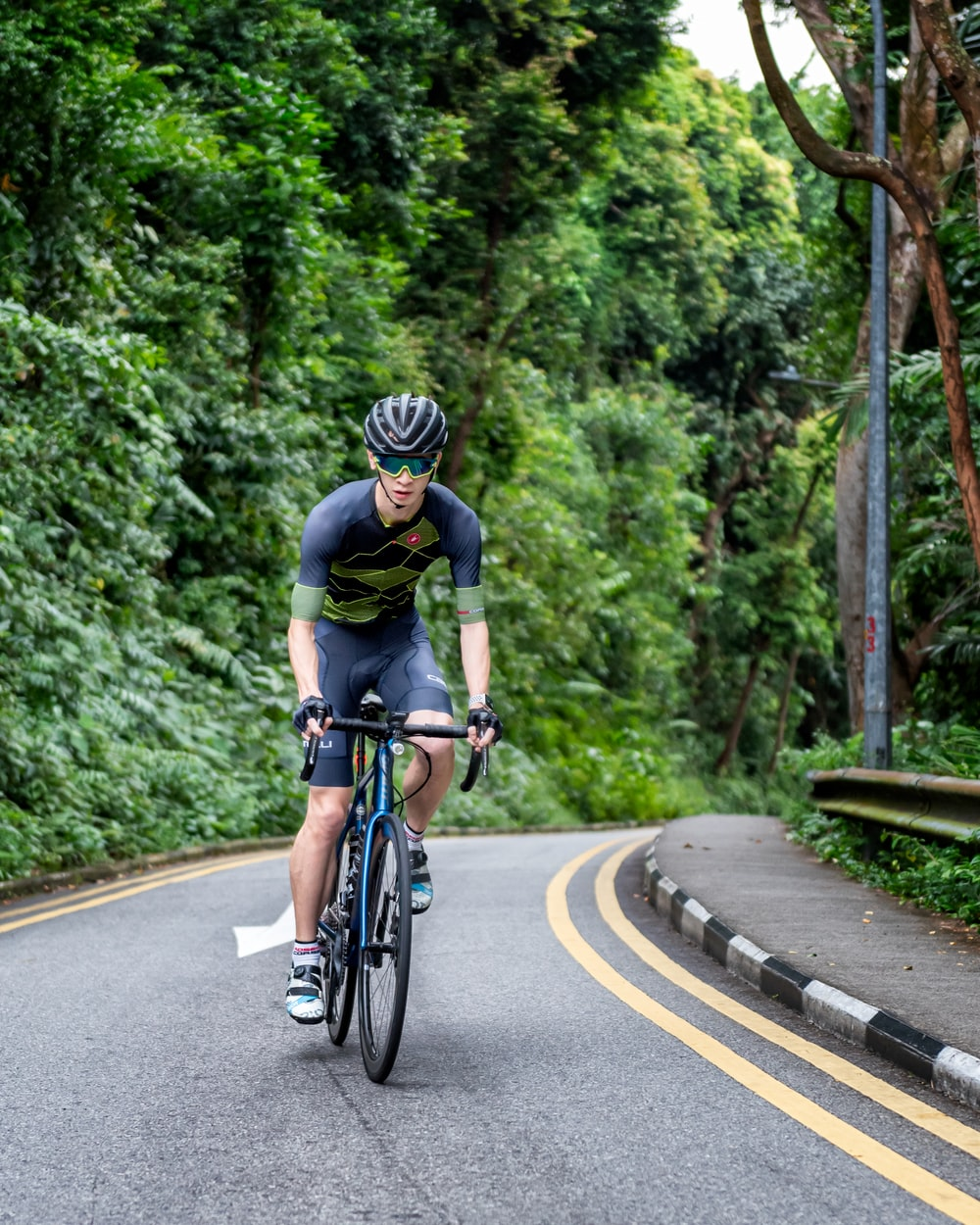 man in black shirt riding on bicycle on road during daytime