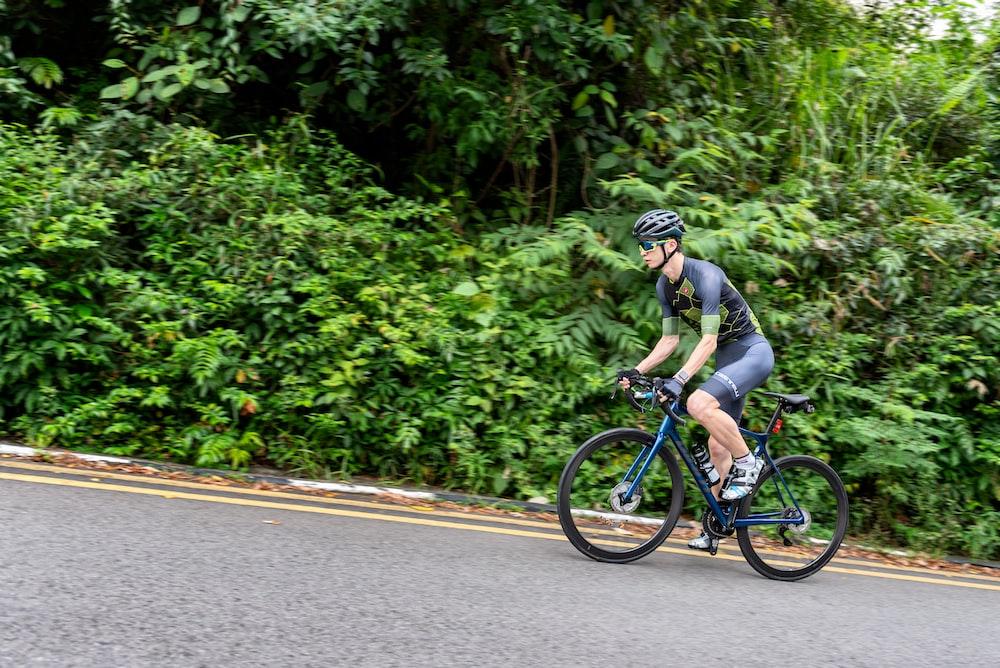 man in gray shirt riding on blue bicycle during daytime