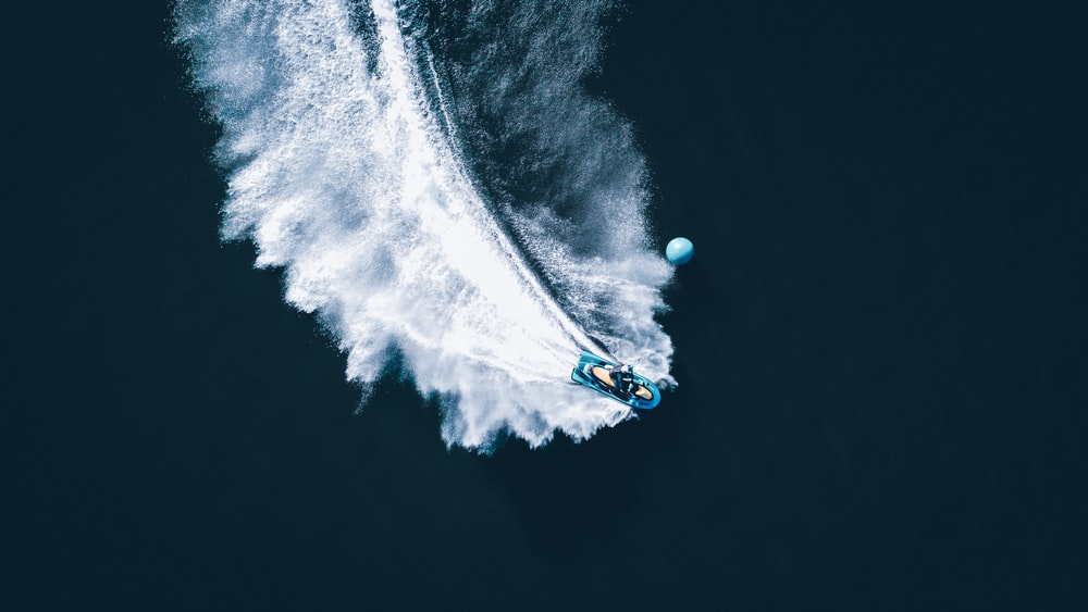 person in blue and white hoodie riding on blue and white boat on water