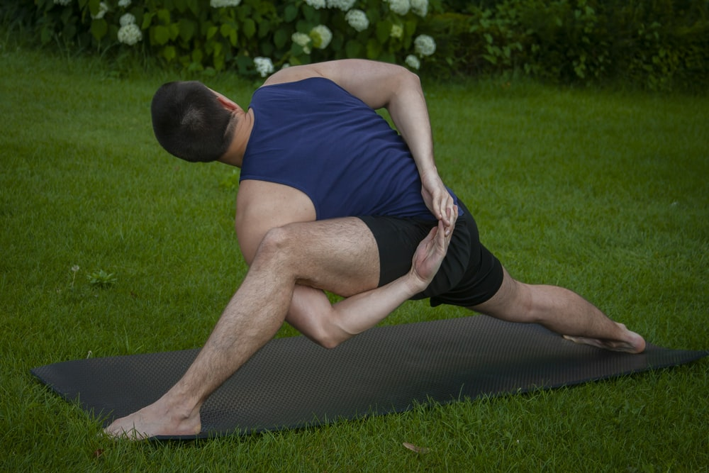 man in blue tank top and black shorts lying on black mat on green grass field