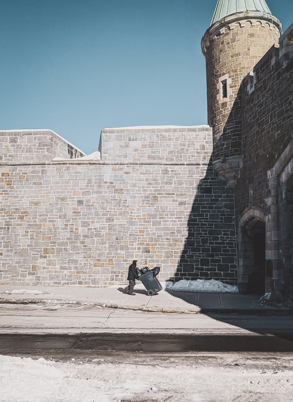 man in black jacket and black pants sitting on concrete bench beside brick wall during daytime