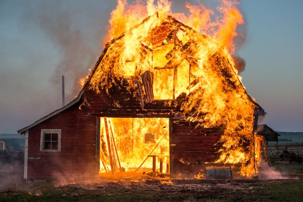 brown wooden house near fire