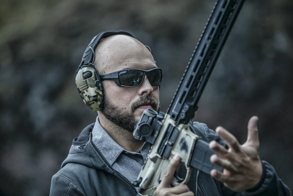 man in blue denim jacket holding black rifle