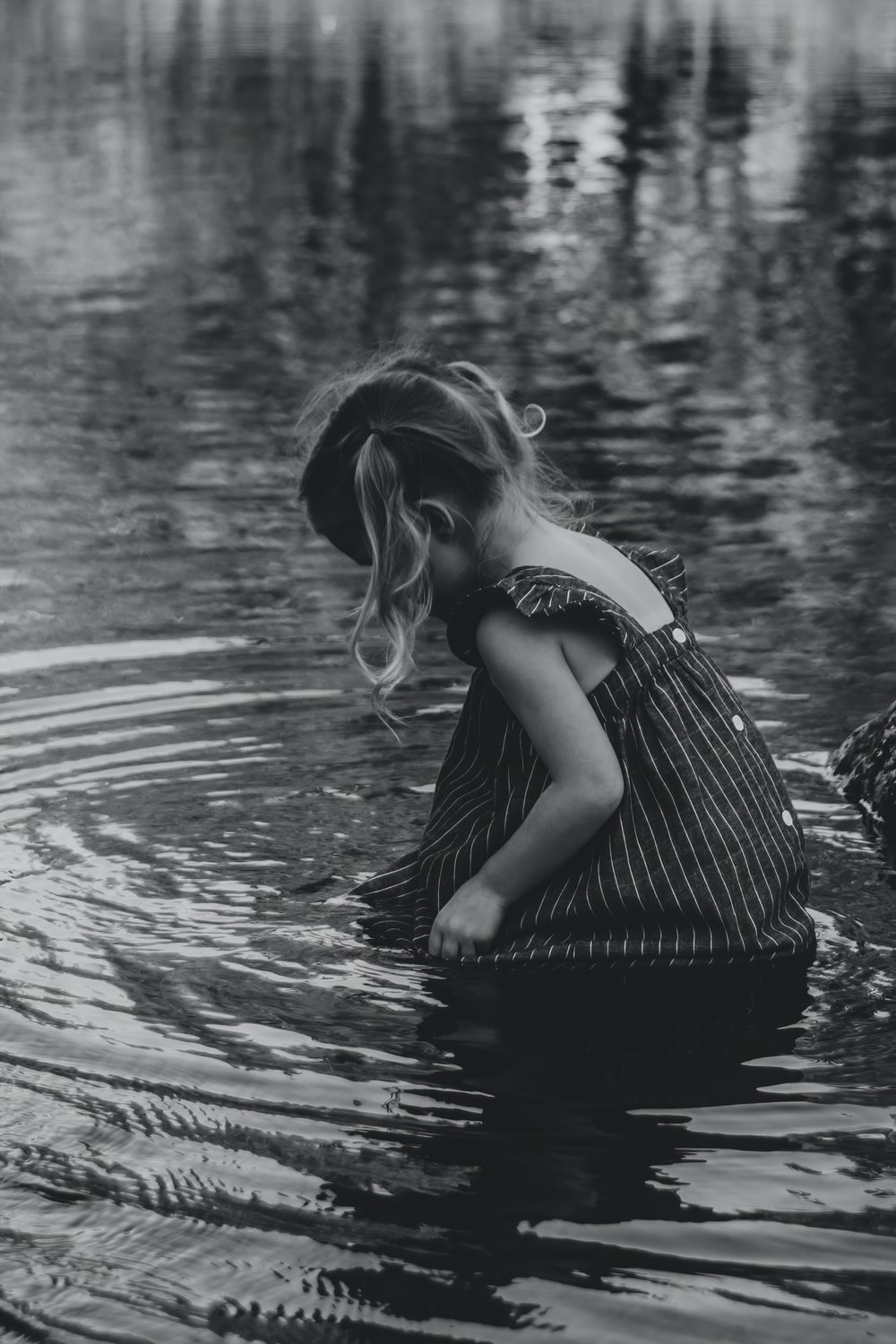 grayscale photo of woman in black and white stripe dress on water