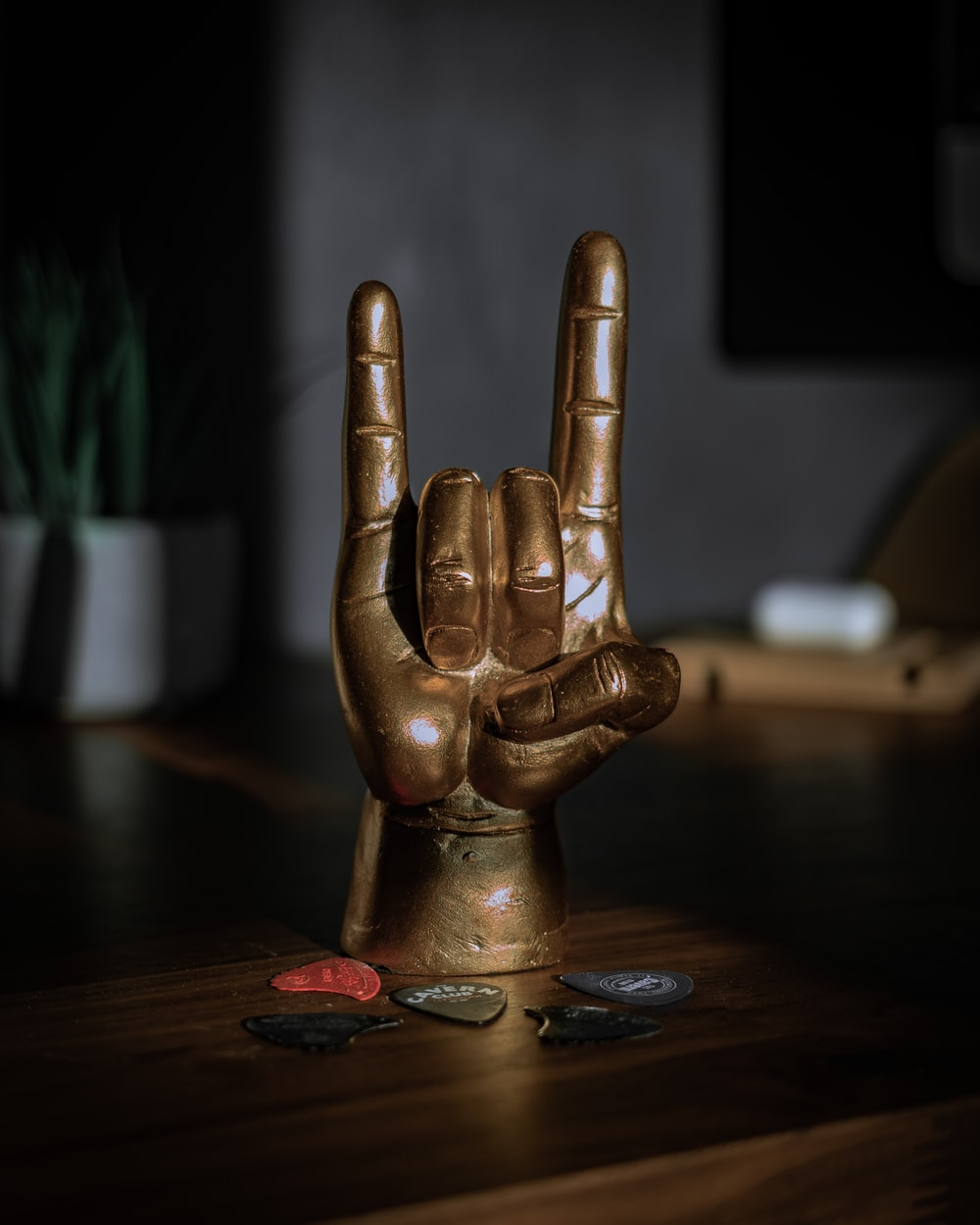 gold human figurine on brown wooden table
