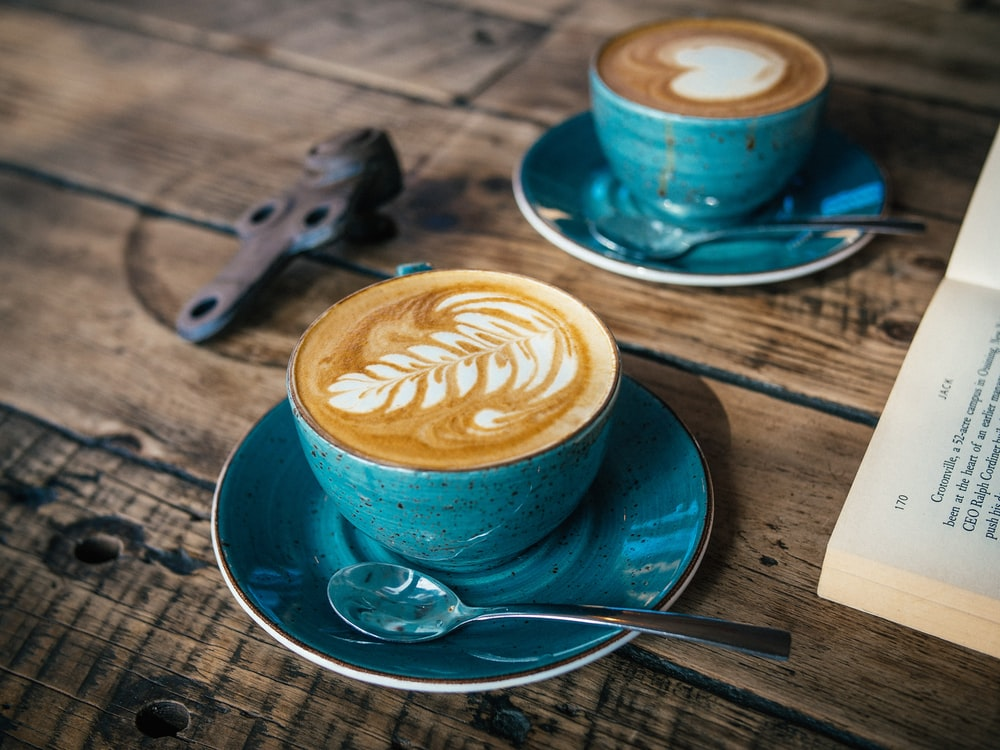 blue ceramic cup with cappuccino on blue saucer
