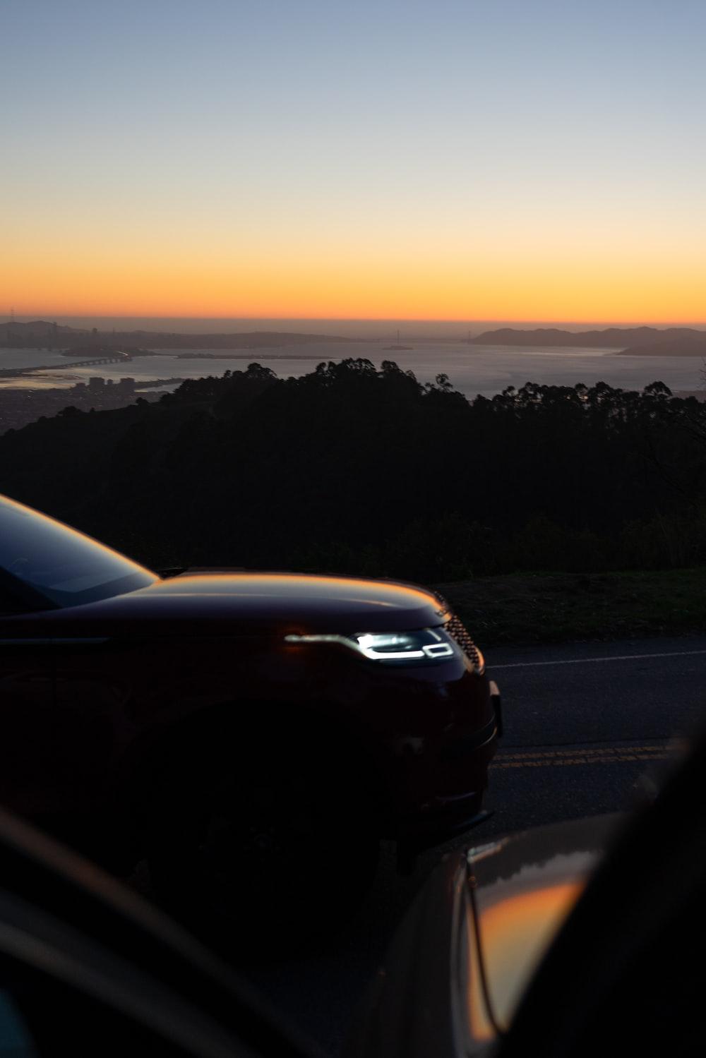 black car on road during sunset