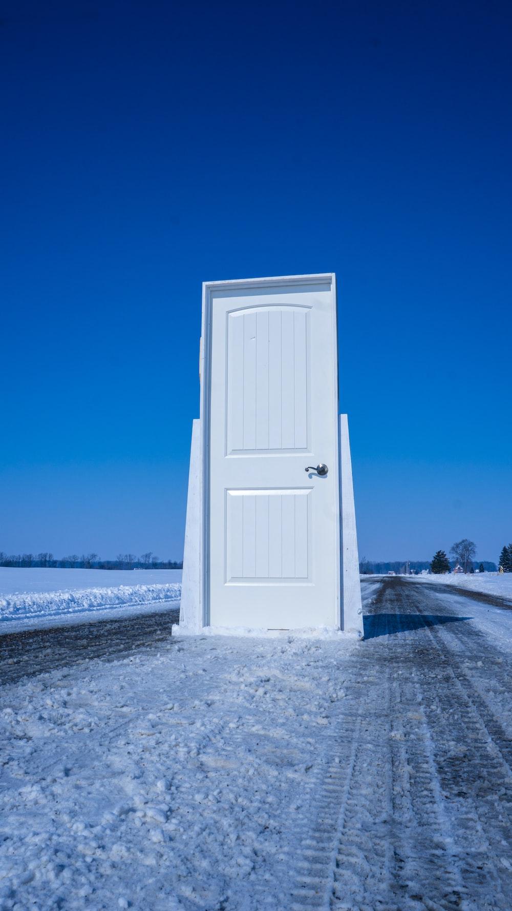 white wooden door near body of water during daytime