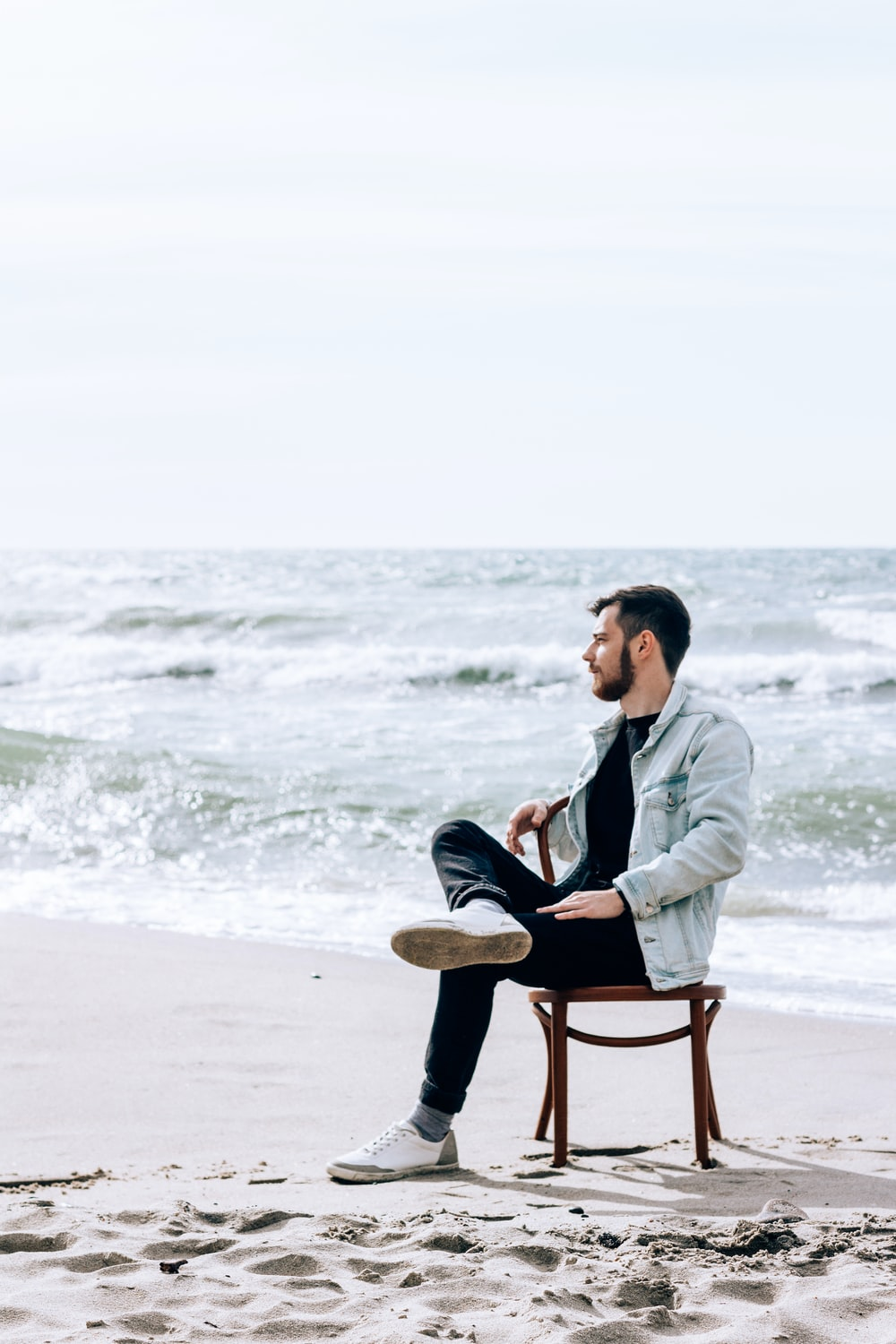 man in gray jacket sitting on brown wooden chair on beach during daytime