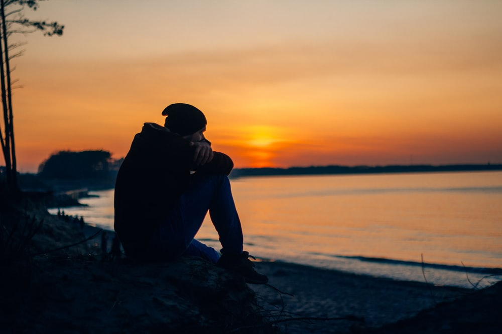 silhouette of man sitting on rock near body of water during sunset