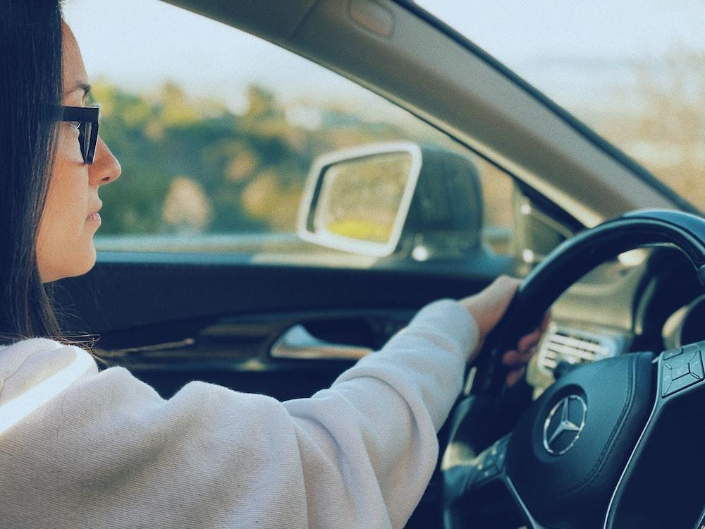 man in white sweater driving car during daytime
