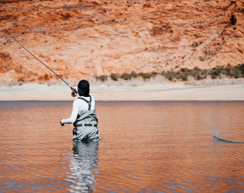 child in white hoodie and black pants fishing on water during daytime