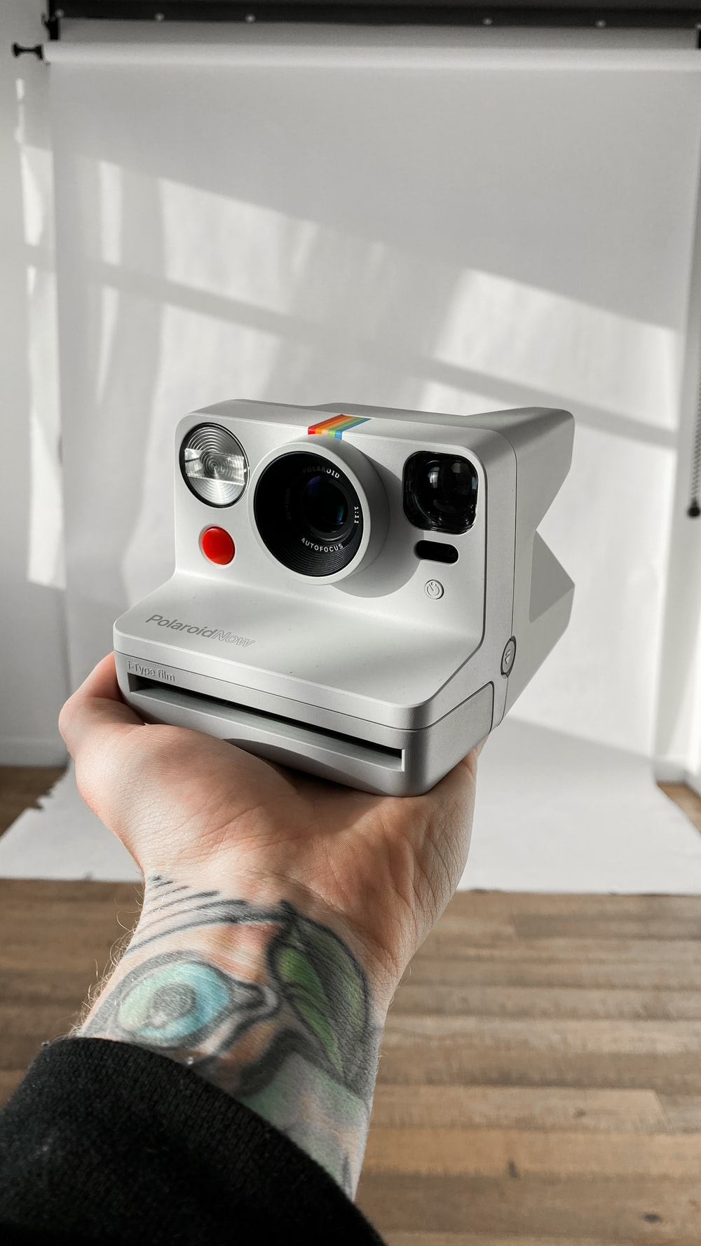 person holding black and white polaroid camera