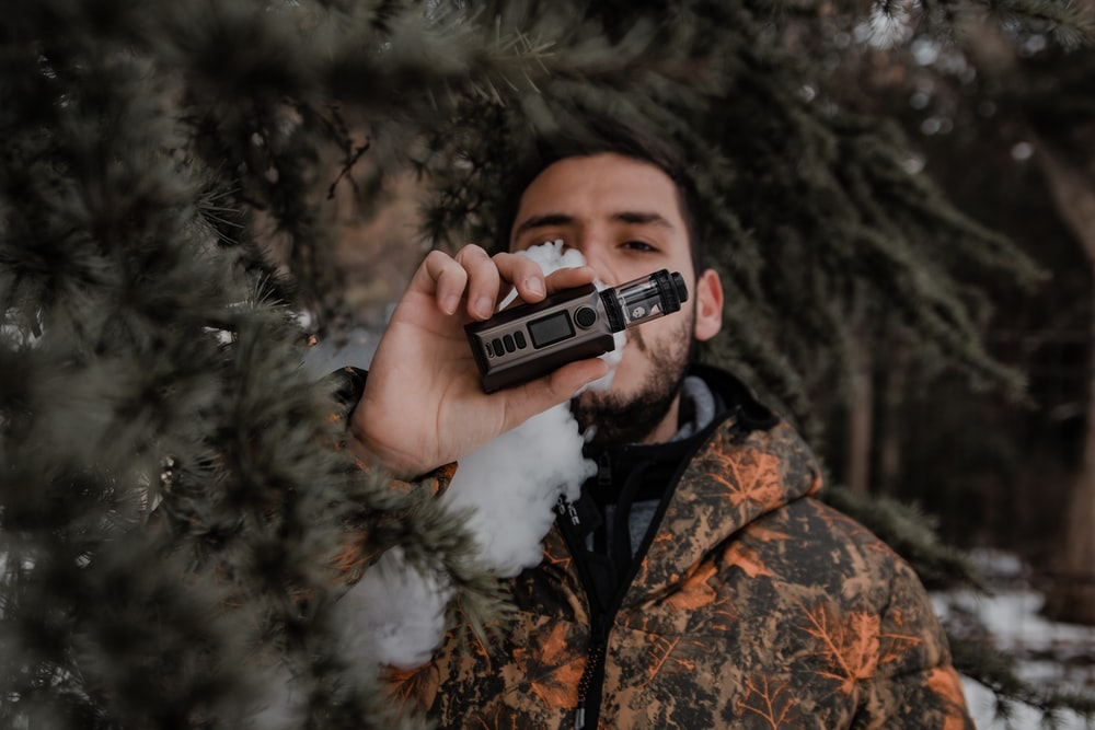 man in brown and black camouflage jacket holding black and silver camera