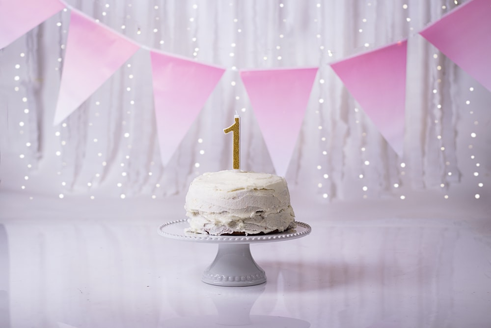 white and gold cake with pink umbrella
