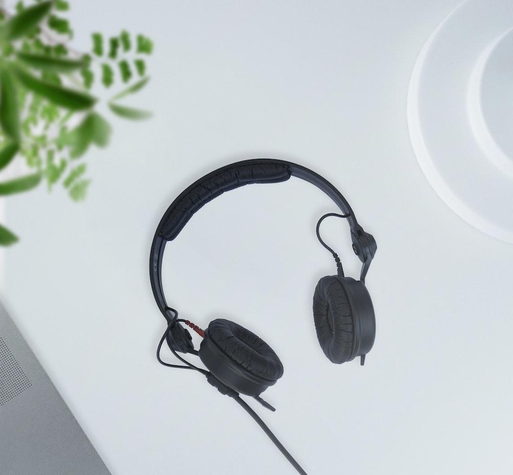 black corded headphones on white table