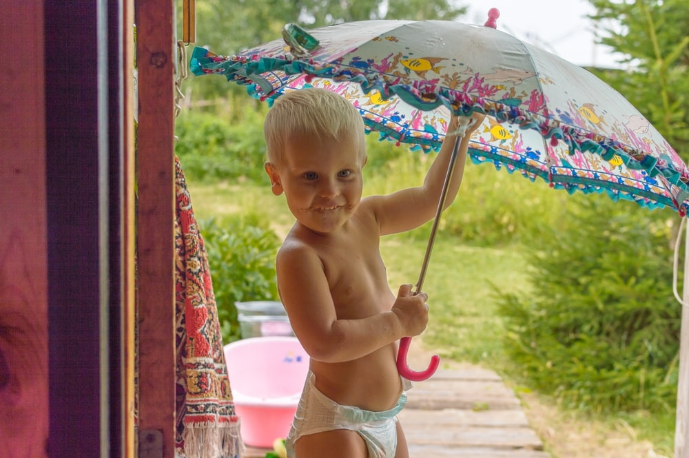 topless baby holding umbrella while sitting on concrete floor during daytime