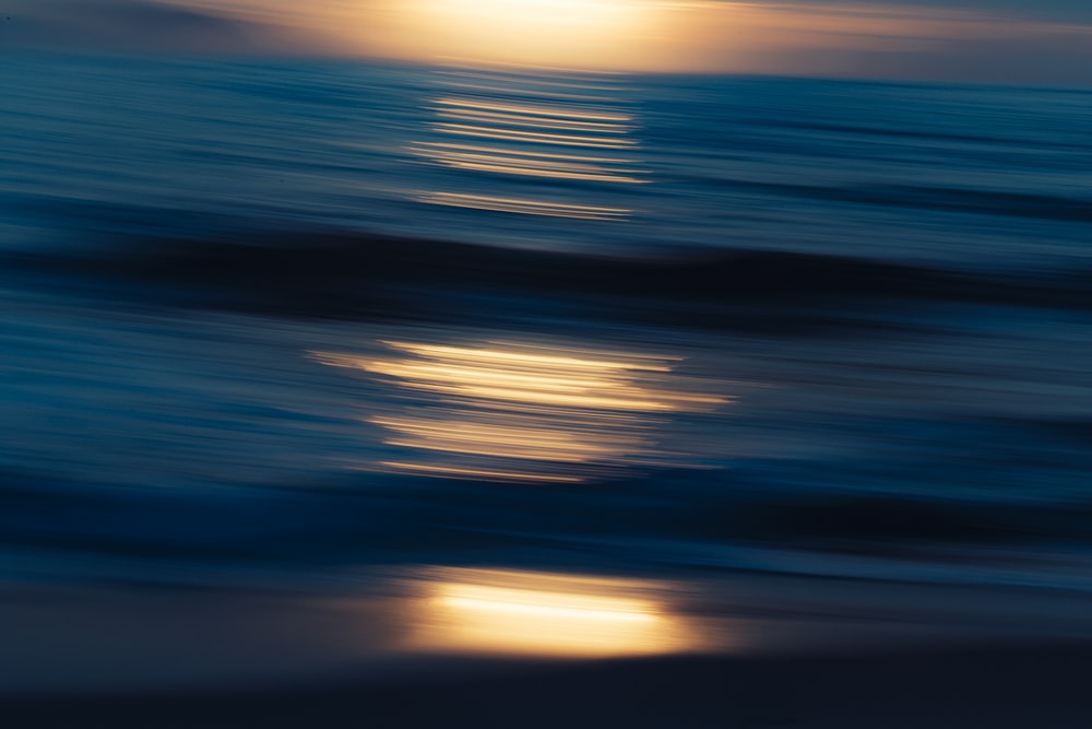 blue and white body of water during sunset
