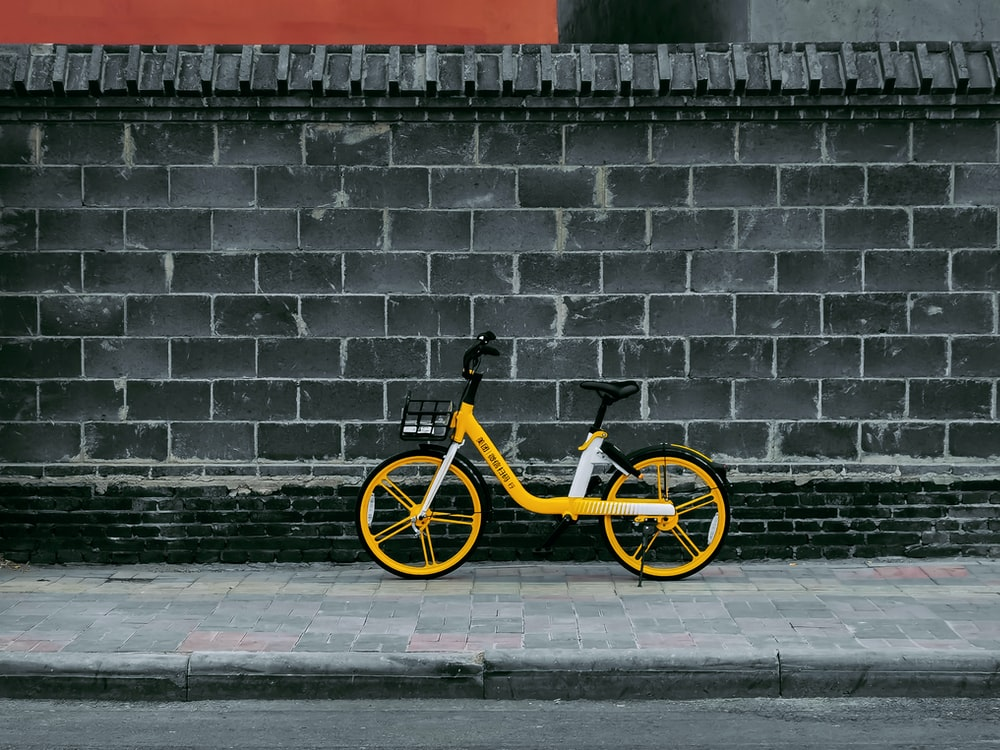 black and yellow bicycle leaning on brick wall