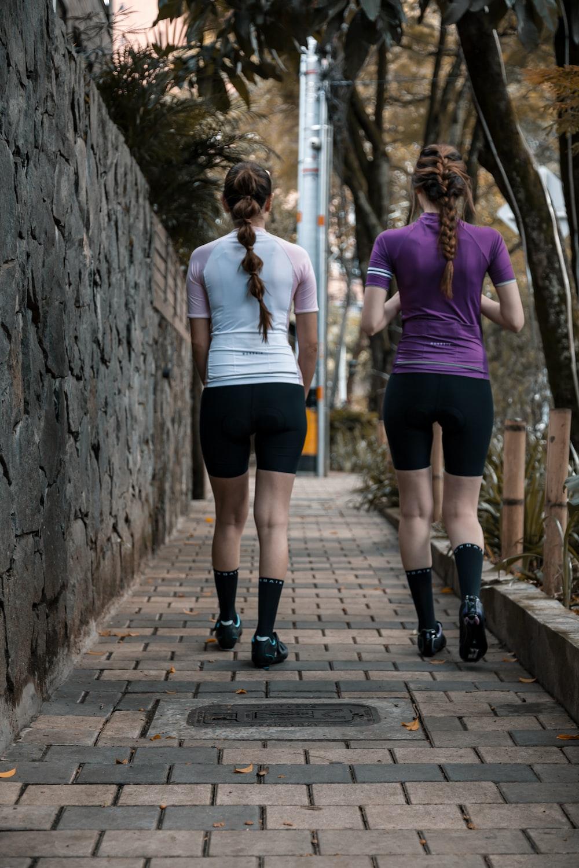 2 women walking on wooden bridge during daytime