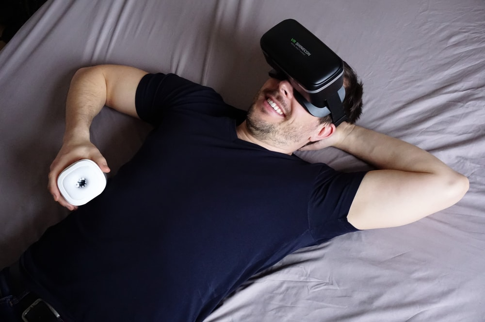 man in black tank top lying on bed