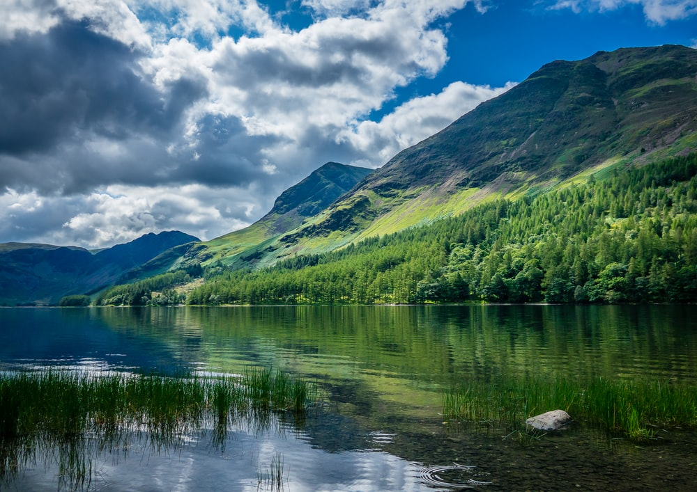 green mountains beside body of water under blue and white sunny cloudy sky during daytime