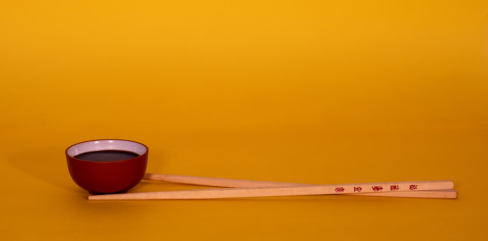 brown wooden chopsticks on red and black ceramic bowl