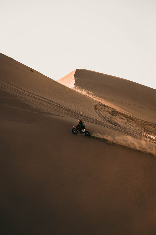 man in black jacket riding black motorcycle on brown sand during daytime