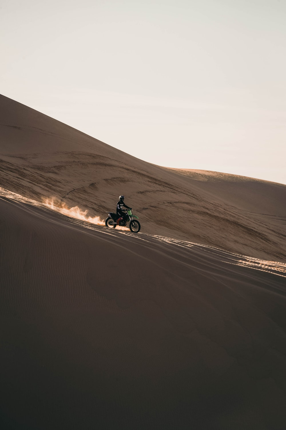 man riding motorcycle on brown sand