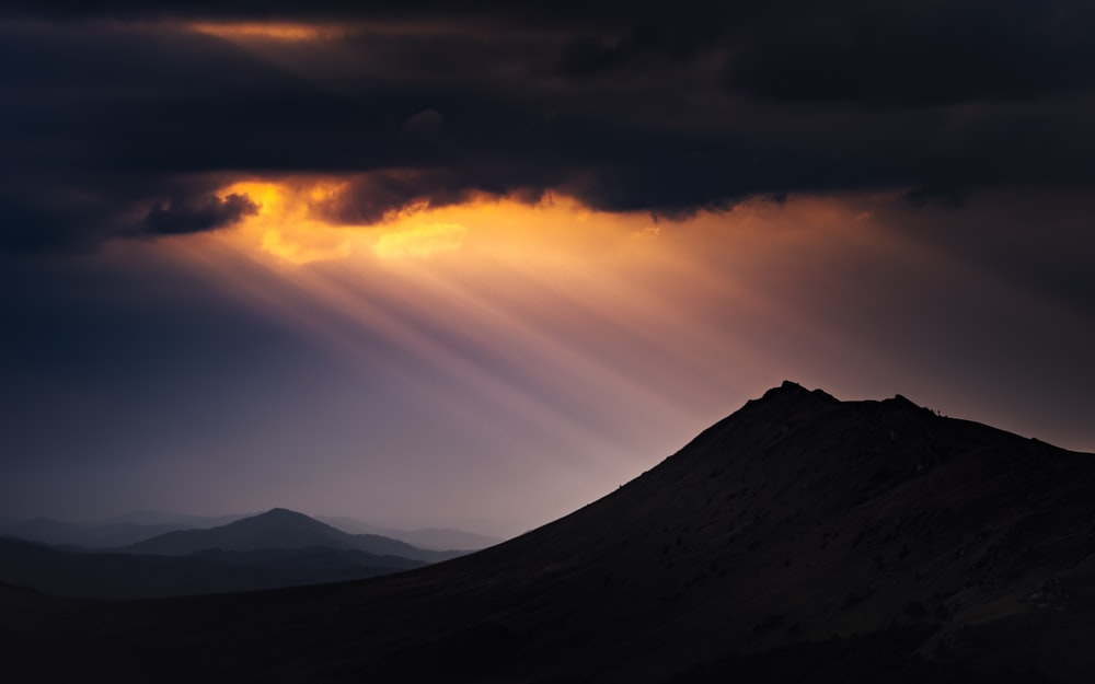 silhouette of mountains under cloudy sky during sunset