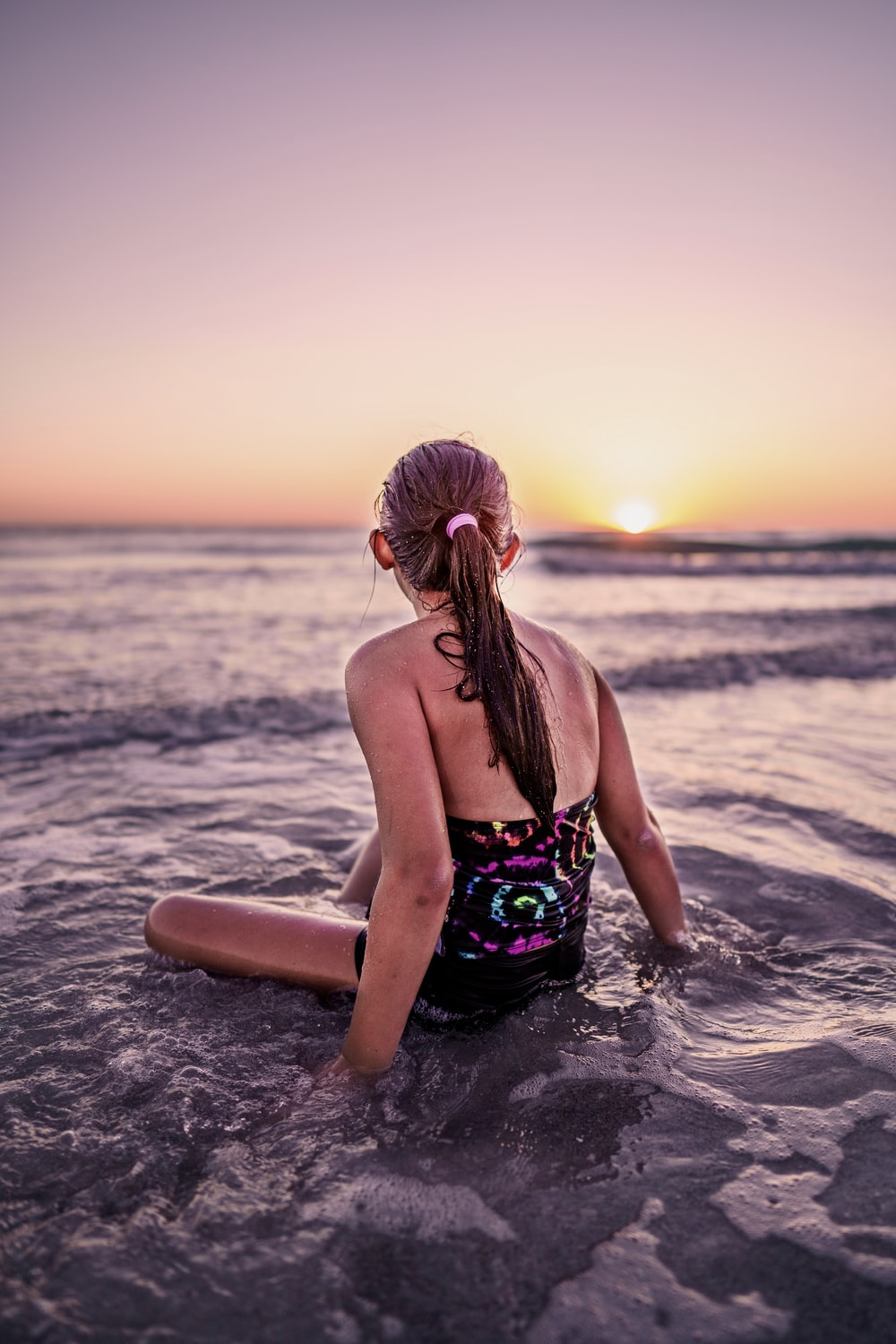 woman in green and black floral bikini sitting on beach during sunset