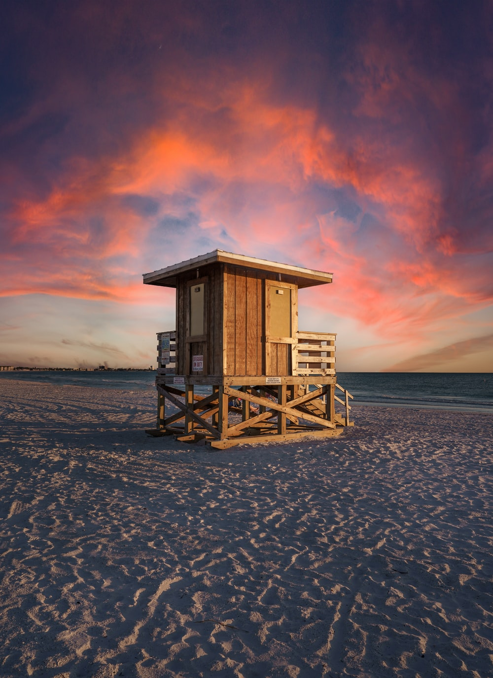 brown wooden lifeguard house on beach shore during sunset