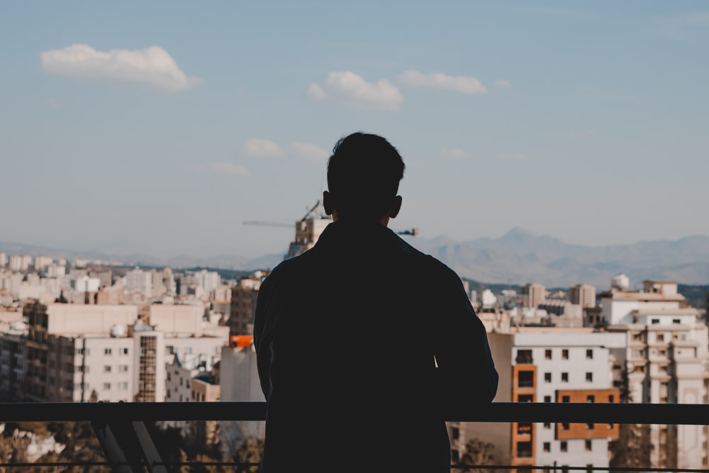 man in black jacket standing on top of building during daytime