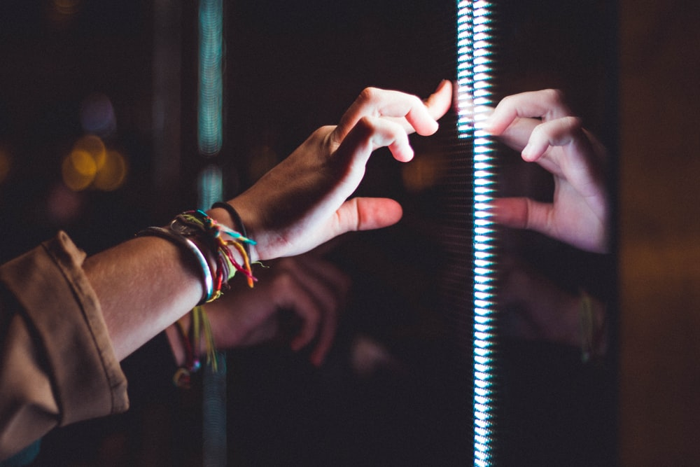 person wearing silver bracelet holding a light