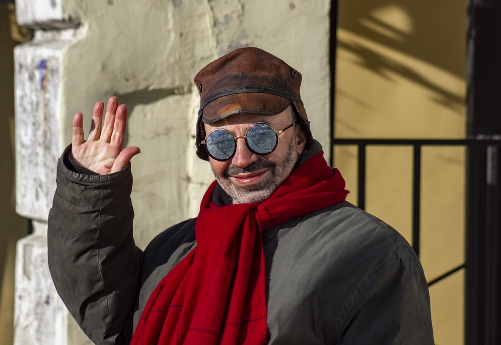 man in black jacket wearing red scarf and black sunglasses
