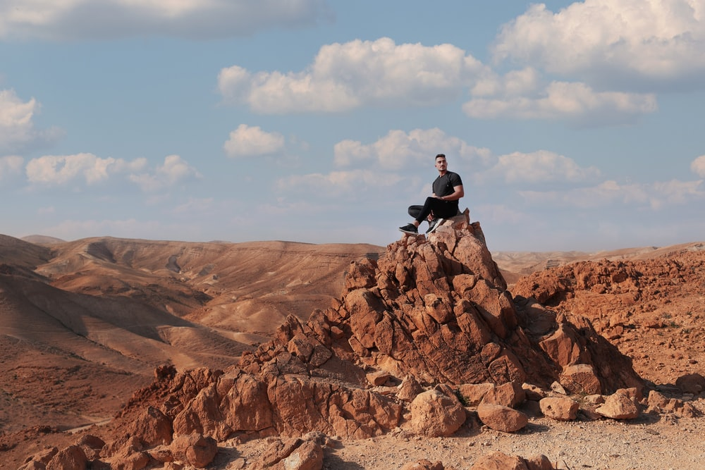 man in black jacket sitting on rock formation during daytime