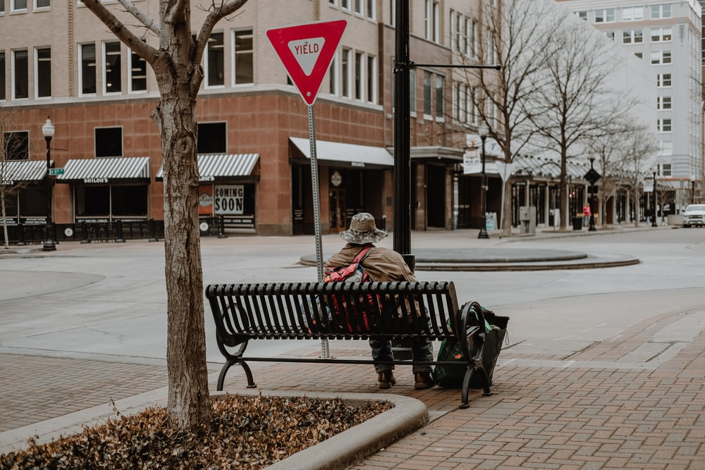 man and woman sitting on bench near road during daytime