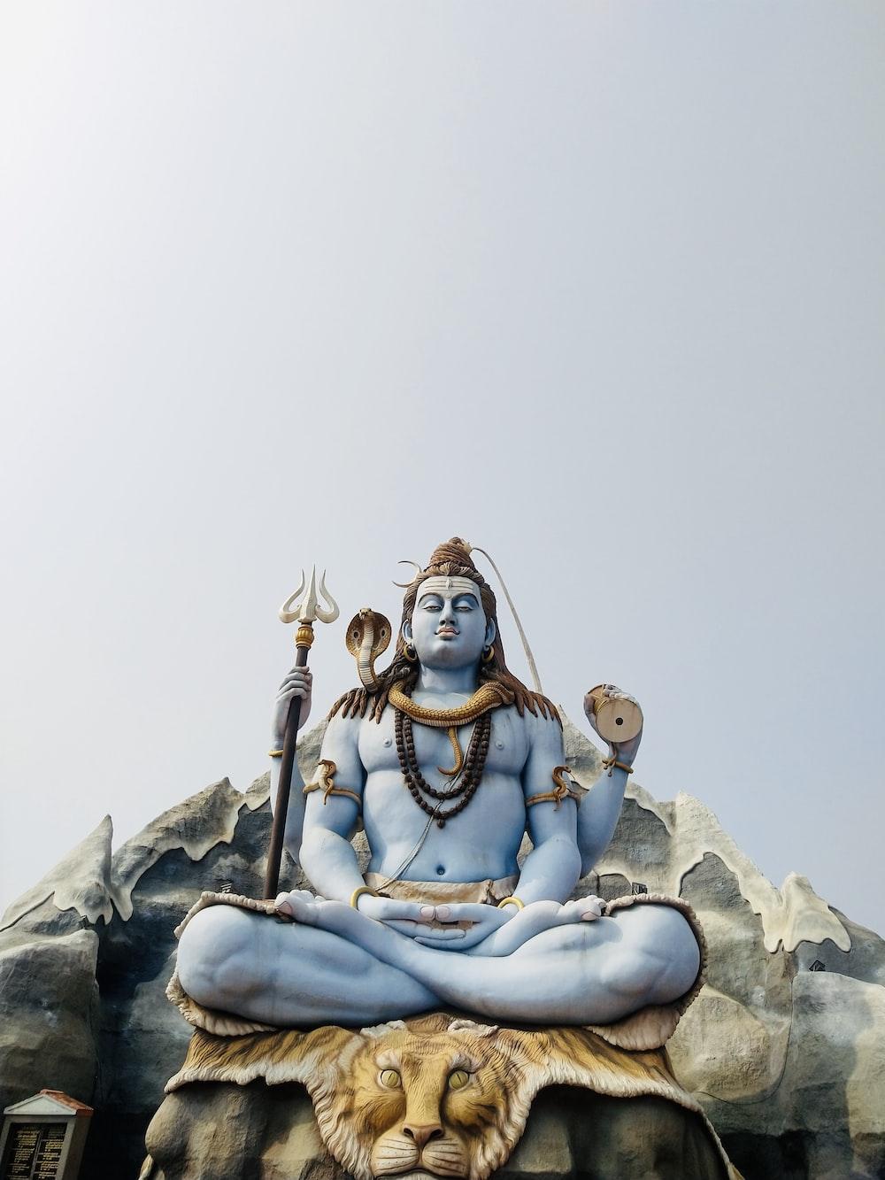 woman in blue dress sitting on rock