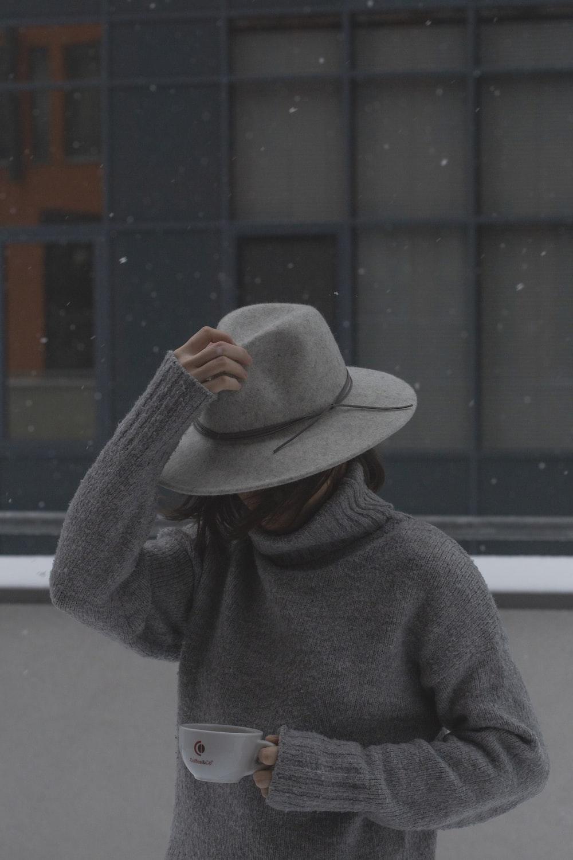 man in gray sweater wearing brown fedora hat
